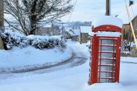old red phone box in snow