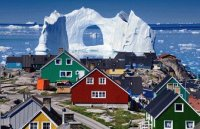 Costal Homes in Greenland as an Iceberg floats by